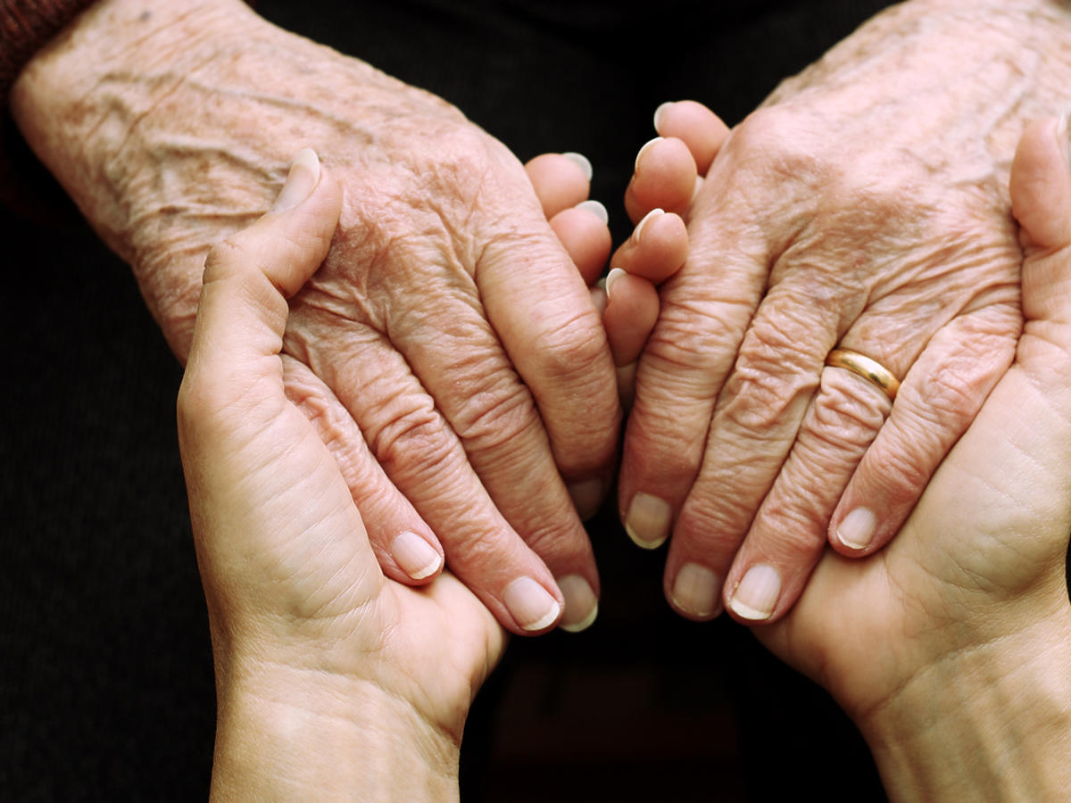 Dłonie dwóch osób, jedne należą do osoby starszej. Osoby trzymają się za ręce.