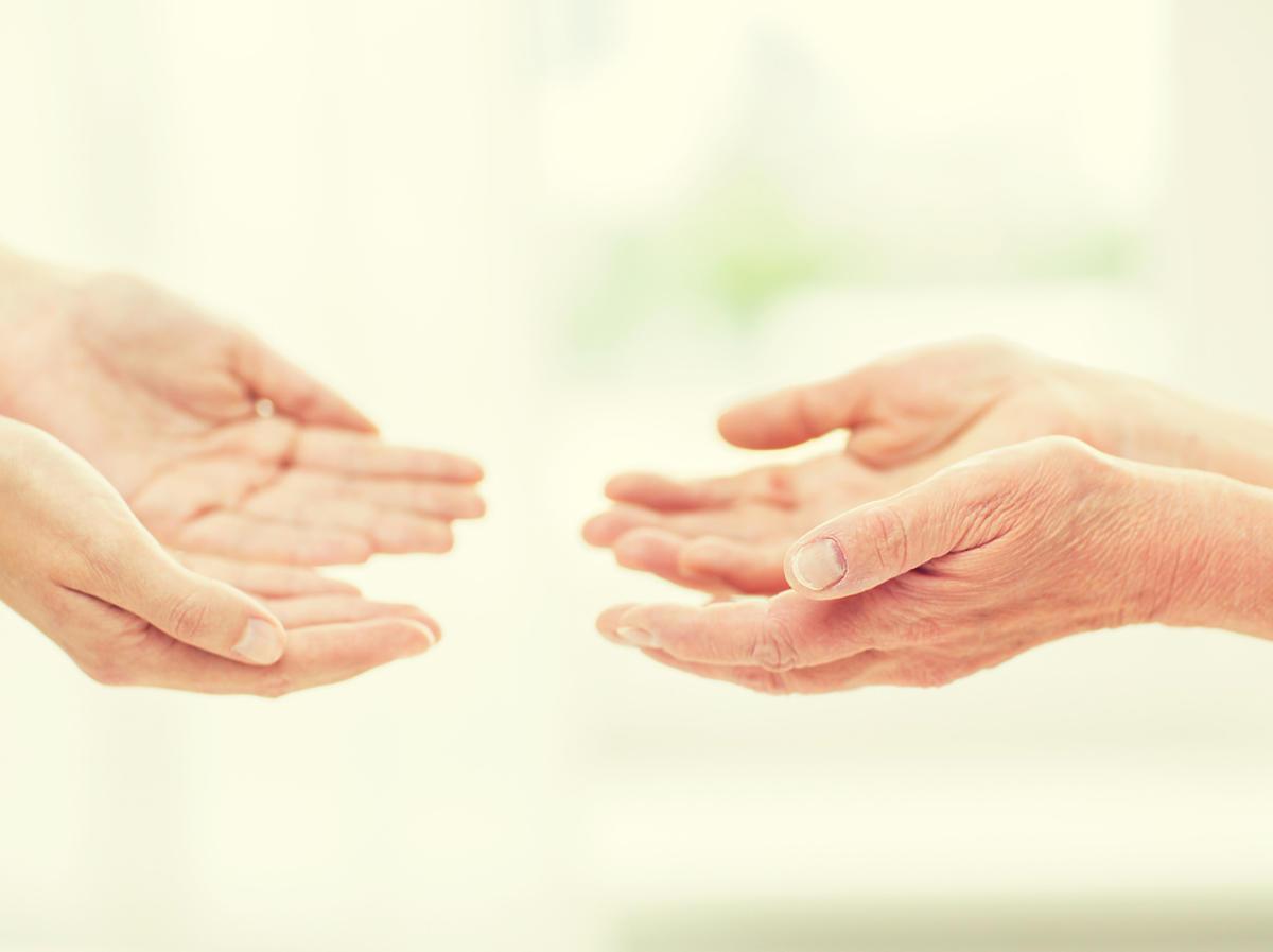 Dłonie młodej i starej osoby zwrócone są do siebie