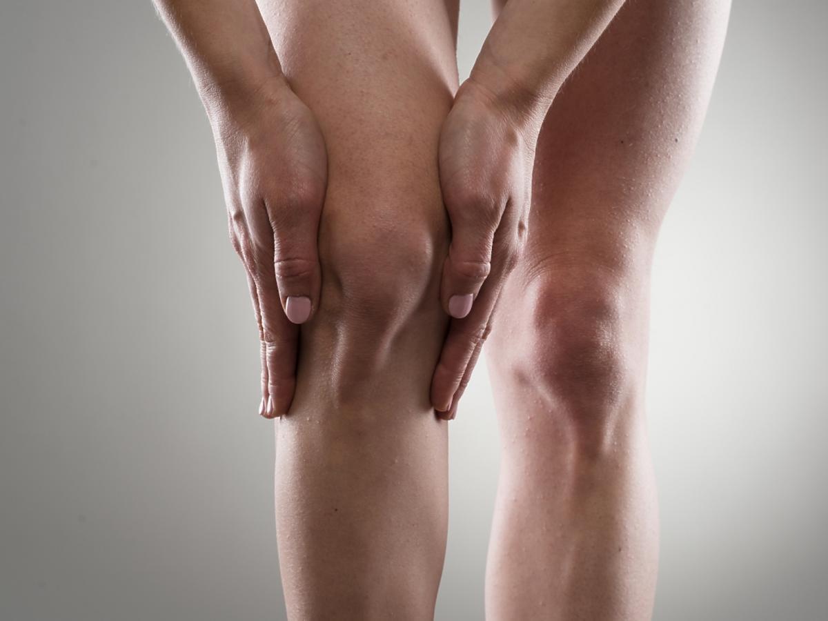 Dłonie trzymające kolano