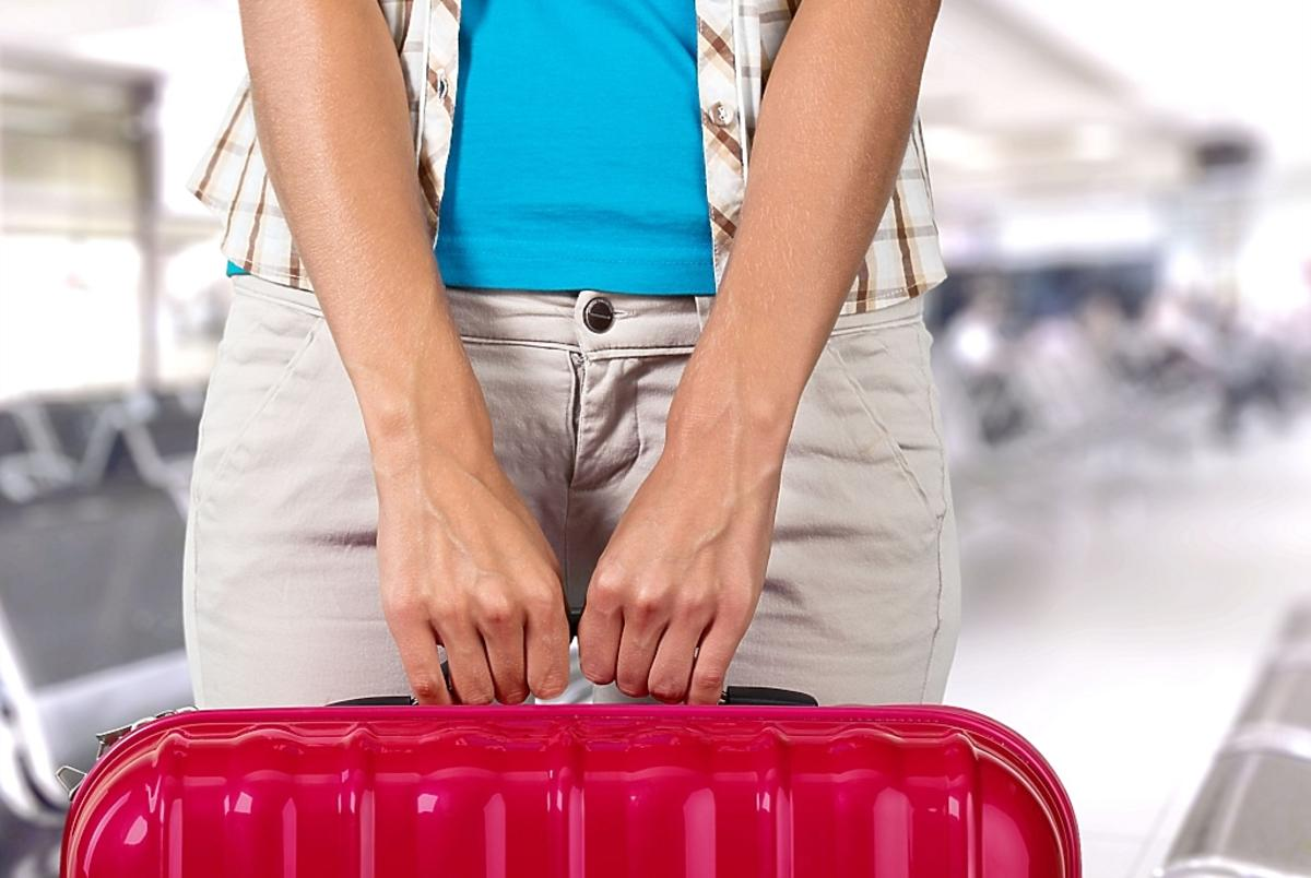 Dłonie trzymające walizkę
