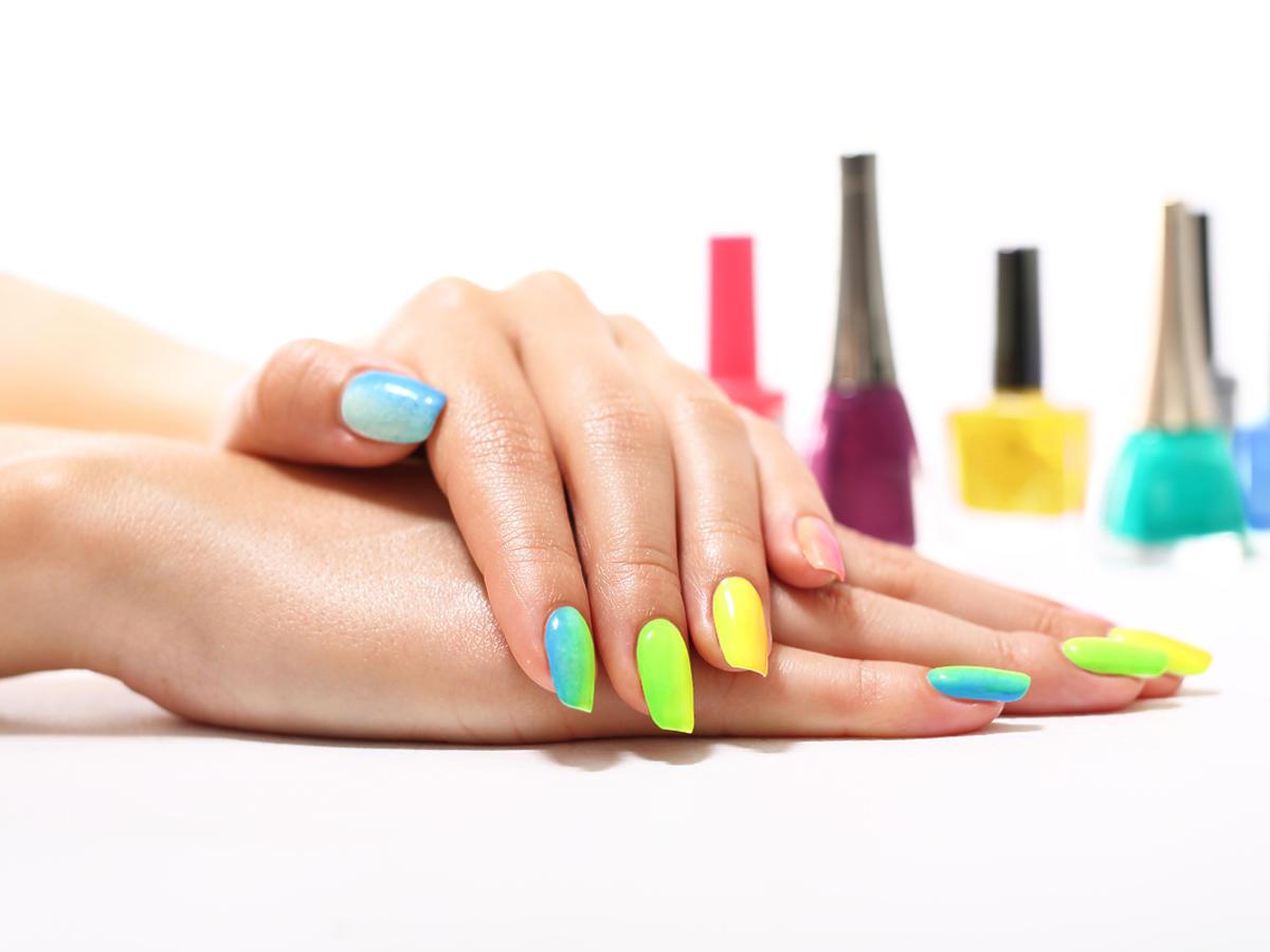 dłonie z pomalowanymi paznokciami, a w tle lakiery