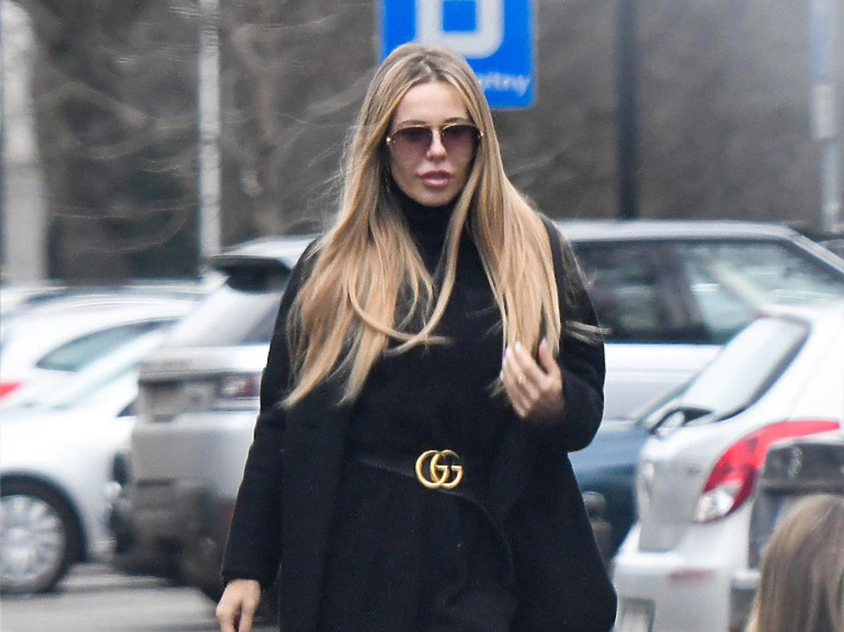Doda w czarnej sukience i czarnym płaszczu na środku ulicy