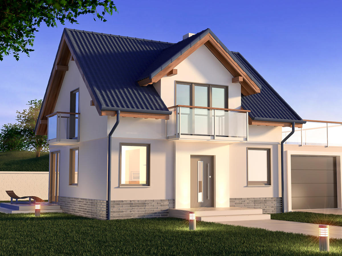 Duży dom jednorodzinny oświetlony lampami.