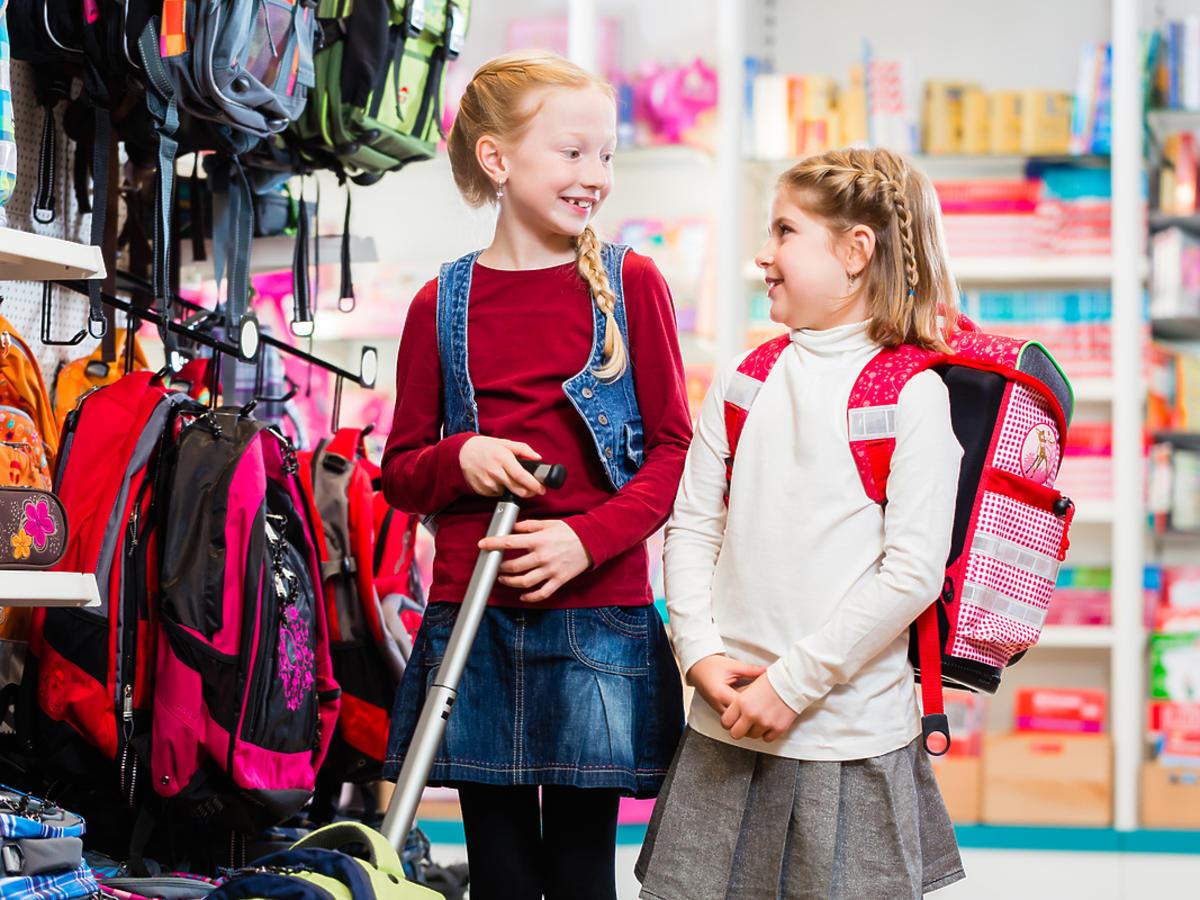 Dwie dziewczynki oglądają plecaki na kółkach w sklepie