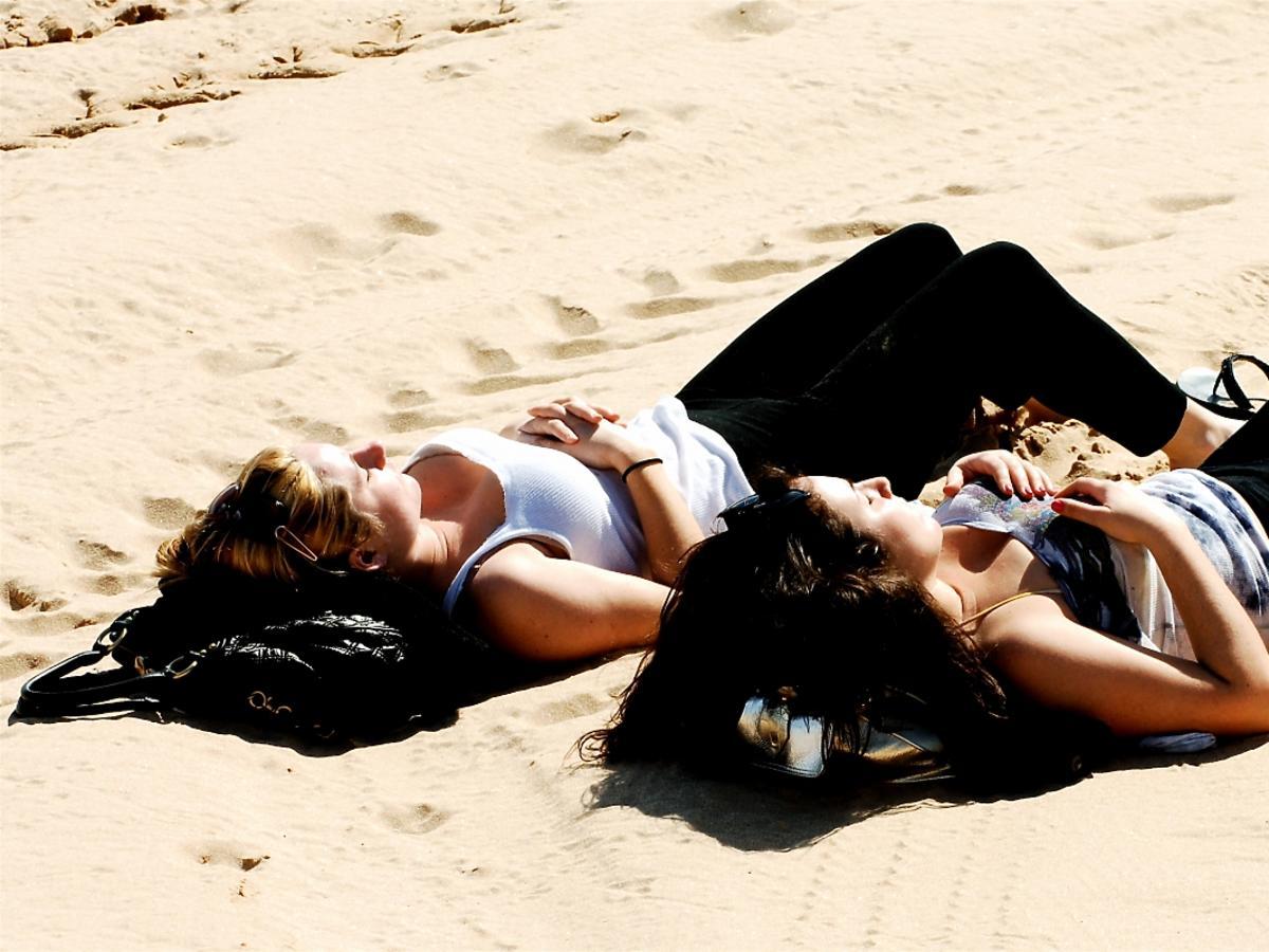 dwie kobiety opalają się na plaży