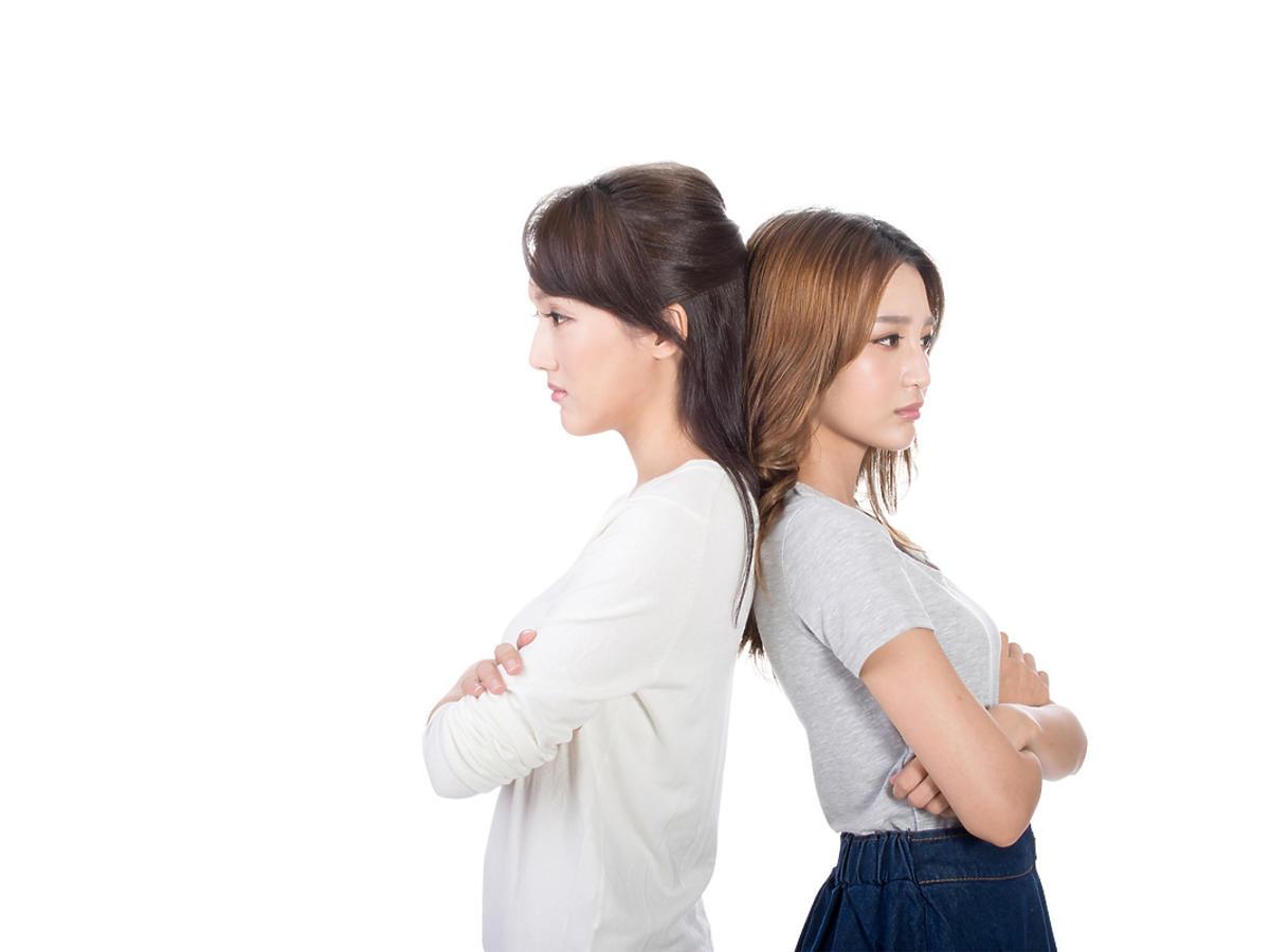 Dwie kobiety stoją do siebie odwrócone plecami.