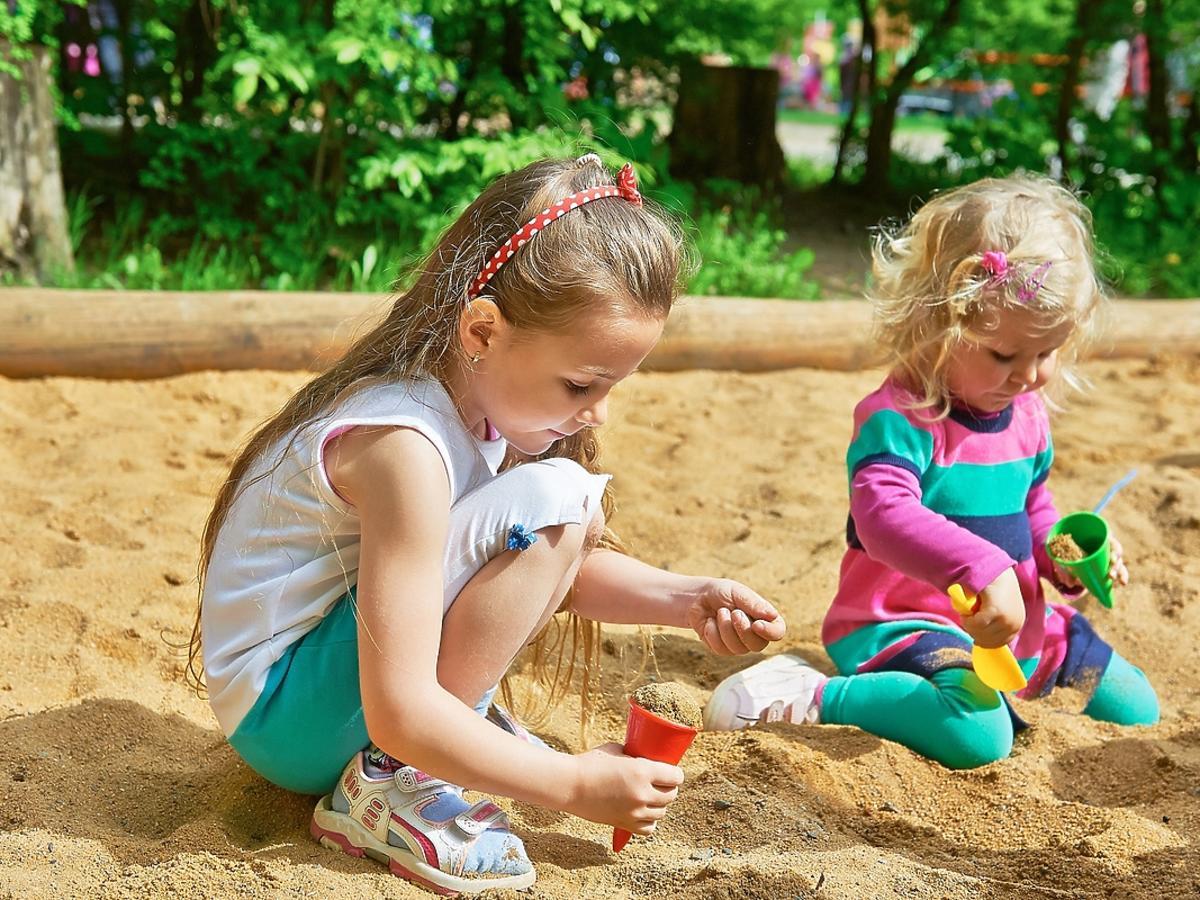 Dwójka dzieci bawi się w ogródkowej piaskownicy.