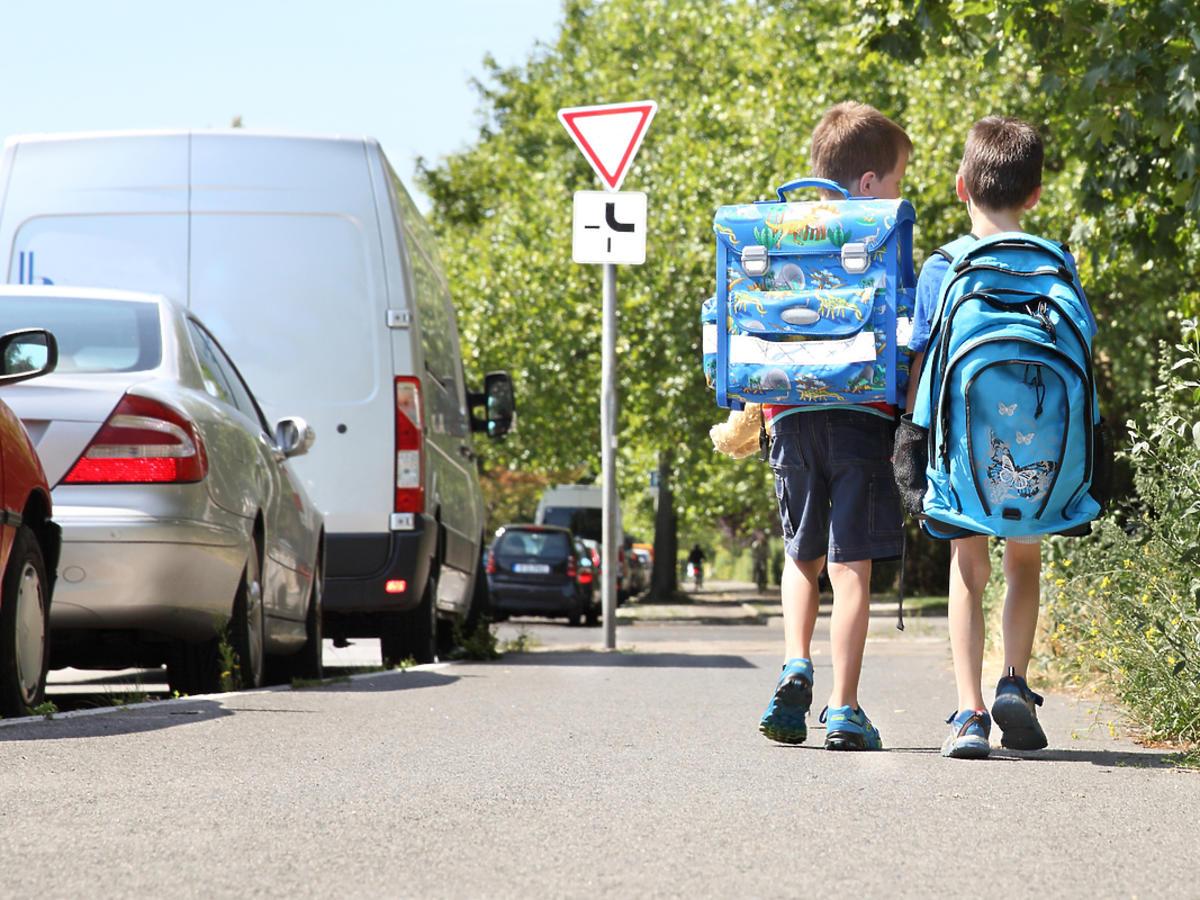 Dwójka dzieci idzie ulicą
