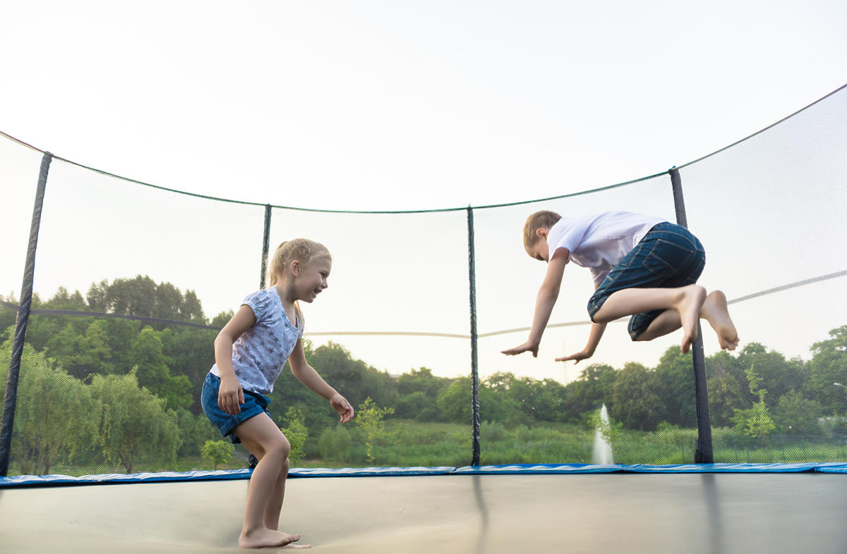 Dwójka dzieci skacze na trampolinie.