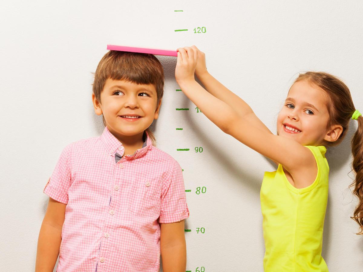 Dwójka uśmiechniętych dzieci mierzy swój wzrost miarką na ścianie. Dziewczynka sprawdza, ile mierzy chłopiec.