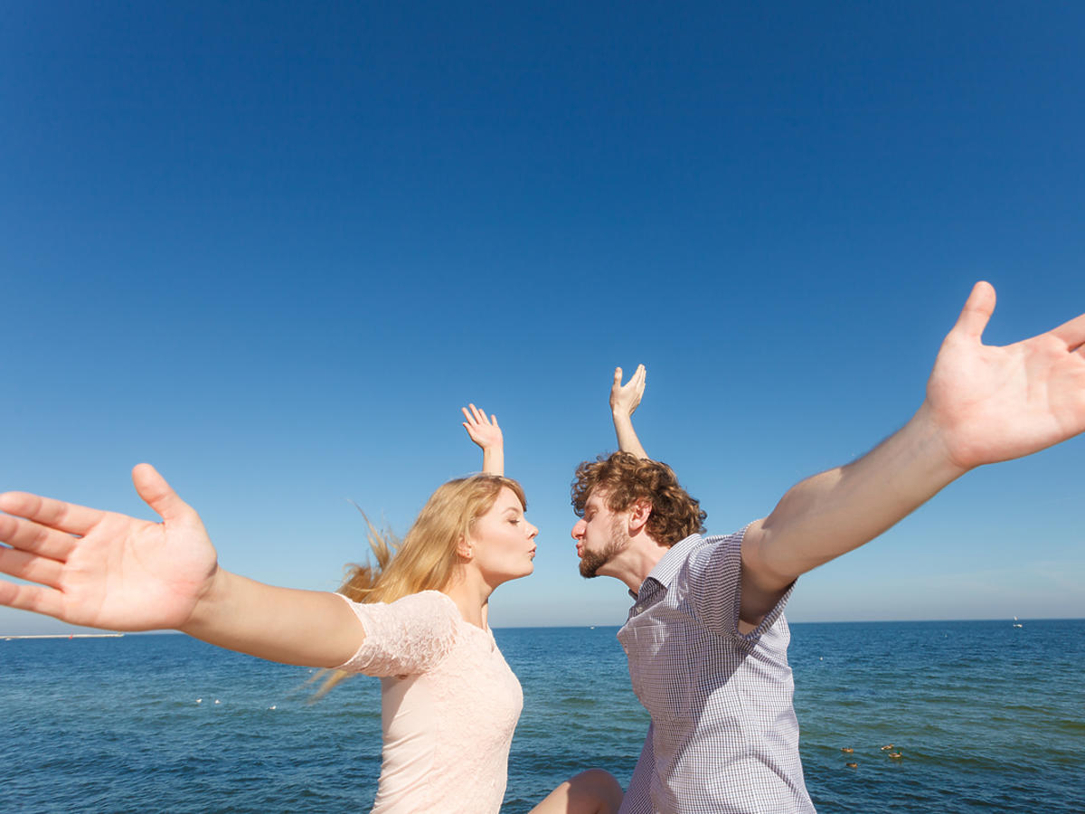 Dwójka zakochanych ludzi z rozłożonymi rękami, zbliżają się do pocałunku.