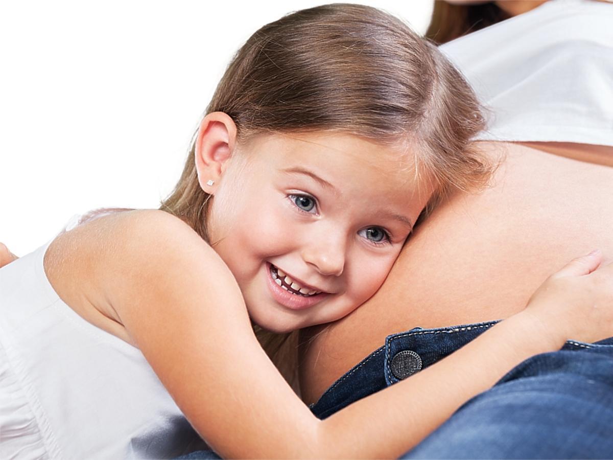 dziecko przytulające brzuch kobiety w ciąży