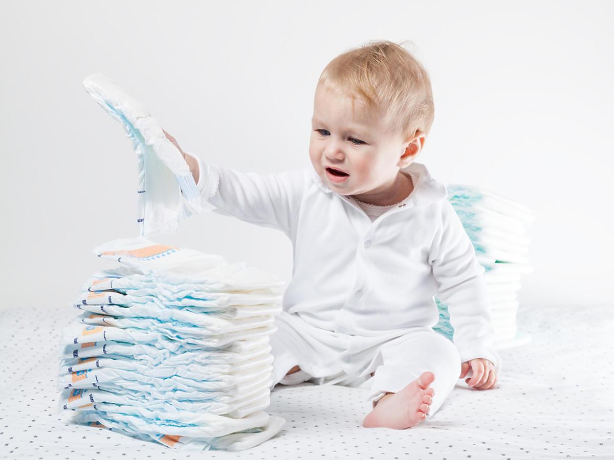 Dziecko siedzi przy stosie pieluszek