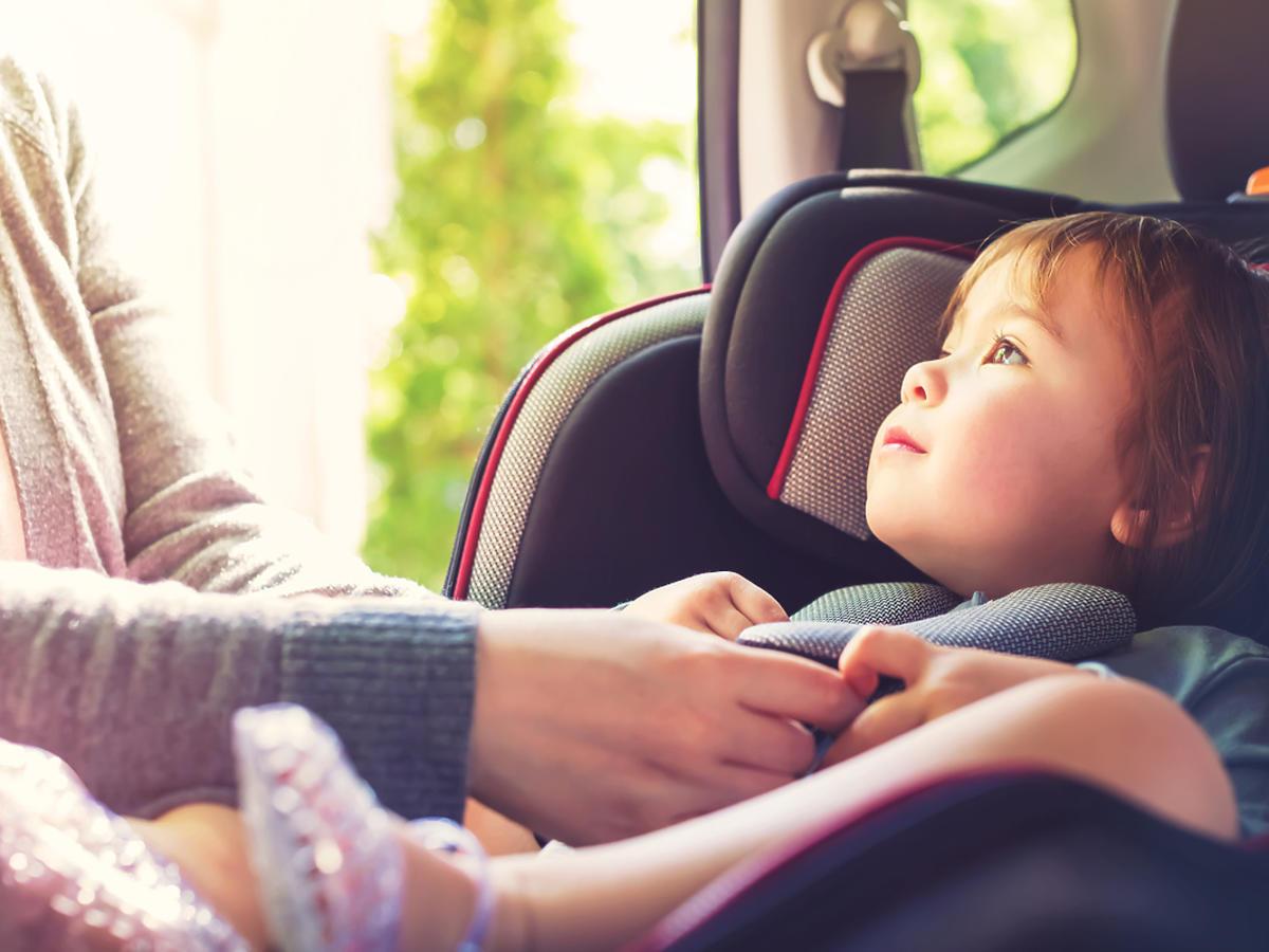 Dziecko siedzi w foteliku samochodowym, mama poprawia mu ubranie.