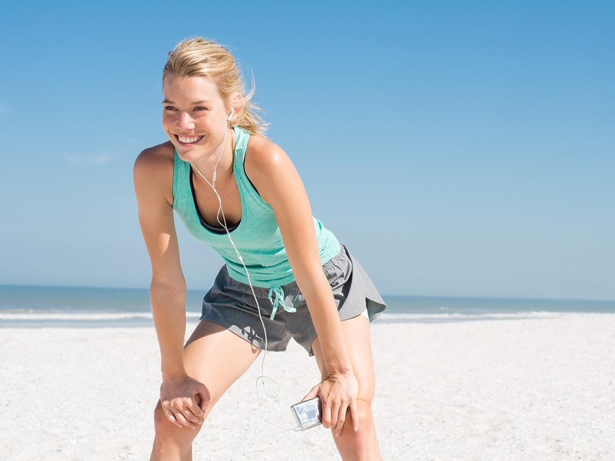 Dziewczyna o blond włosach trenuje latem na plaży.