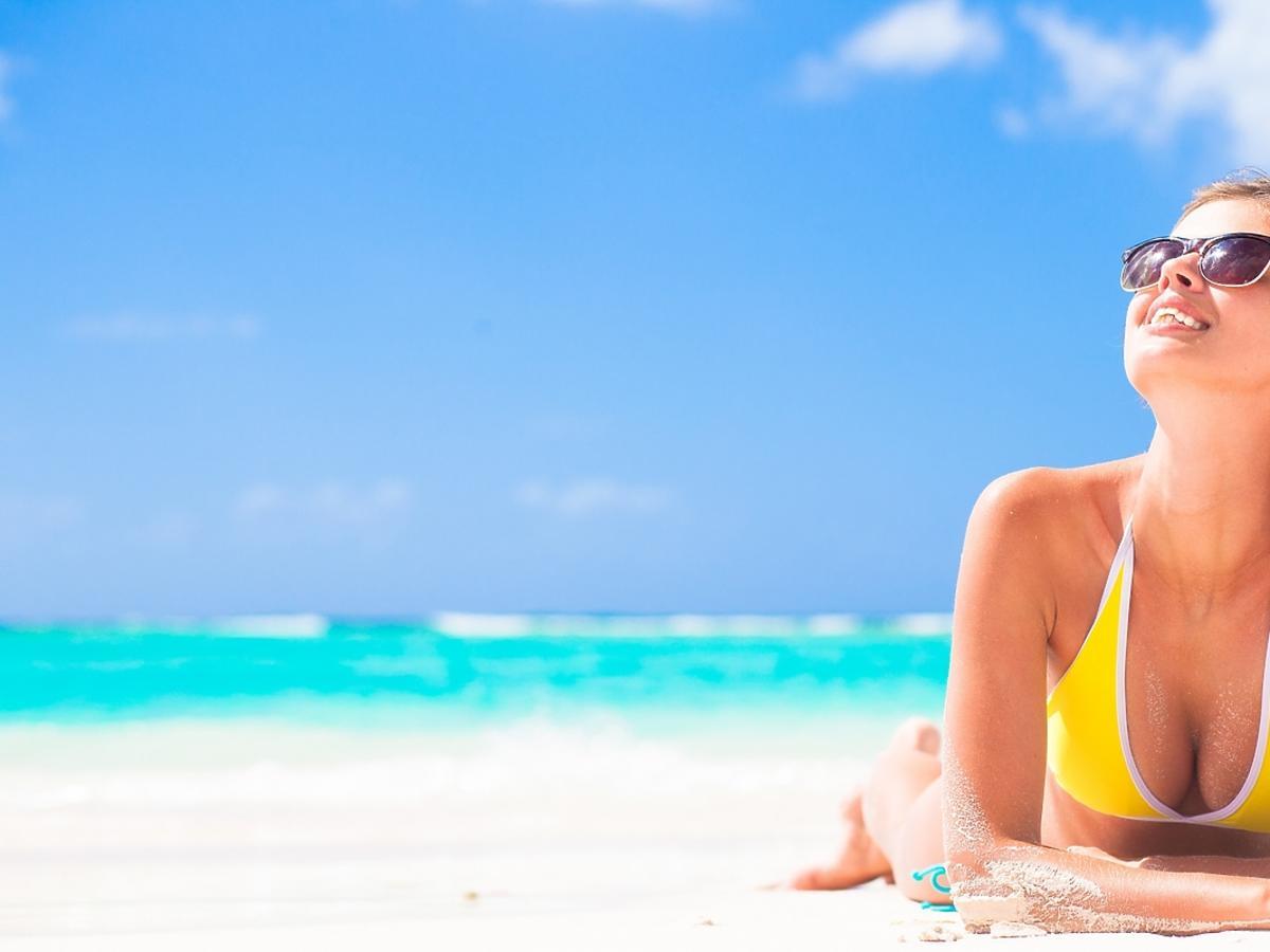 Dziewczyna opala się na plaży.