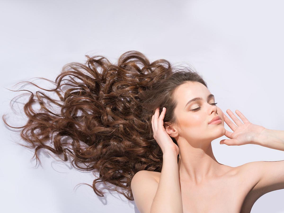 Dziewczyna rozpuszcza długie, brązowe, kręcone włosy