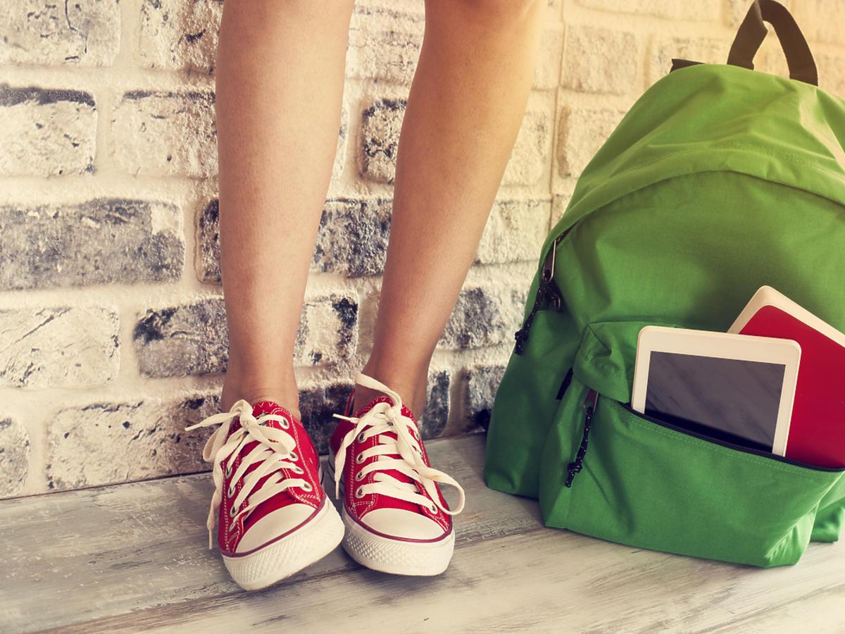 Dziewczyna stoi w trampach, obok niej leży plecak.