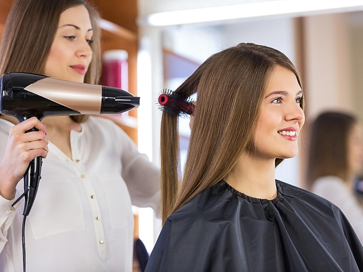 dziewczyna suszy zdrowe włosy u fryzjera