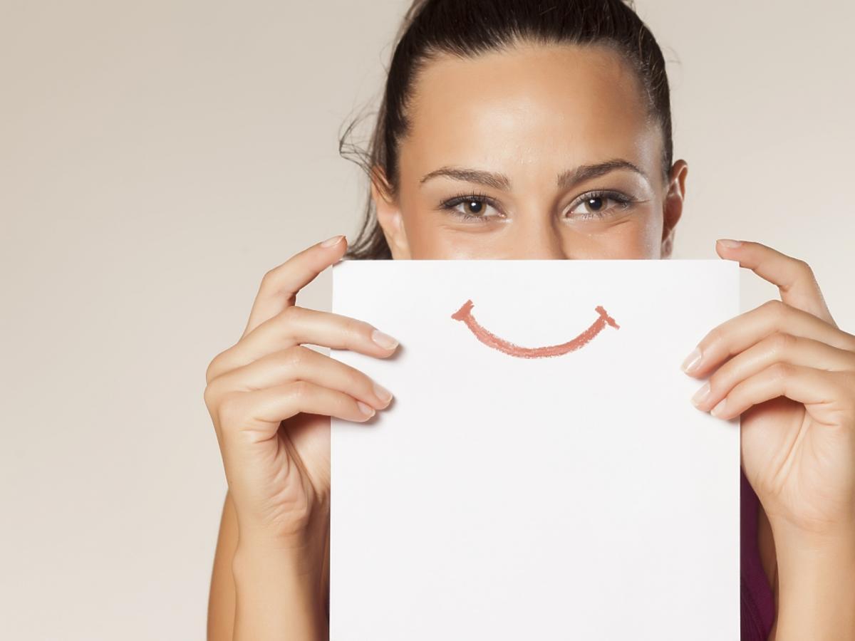 dziewczyna trzyma w ręku kartkę z uśmiechem