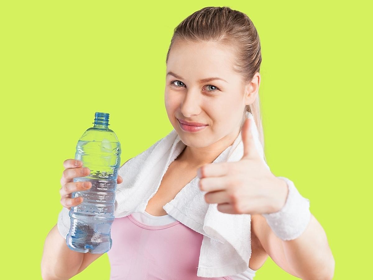 dziewczyna uśmiecha się i trzyma w rękach wodę mineralną