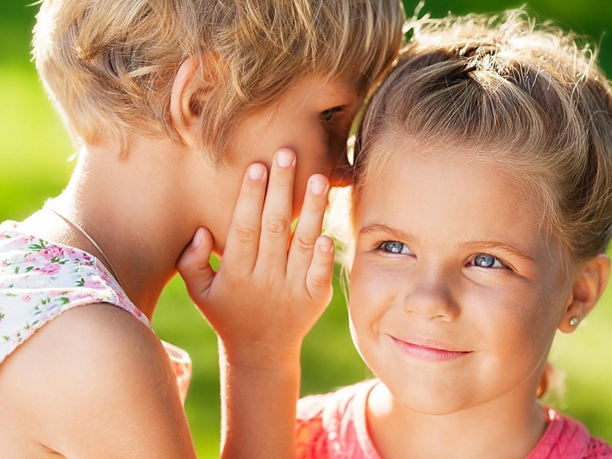 Dziewczynka szepcze na ucho drugiej dziewczynce