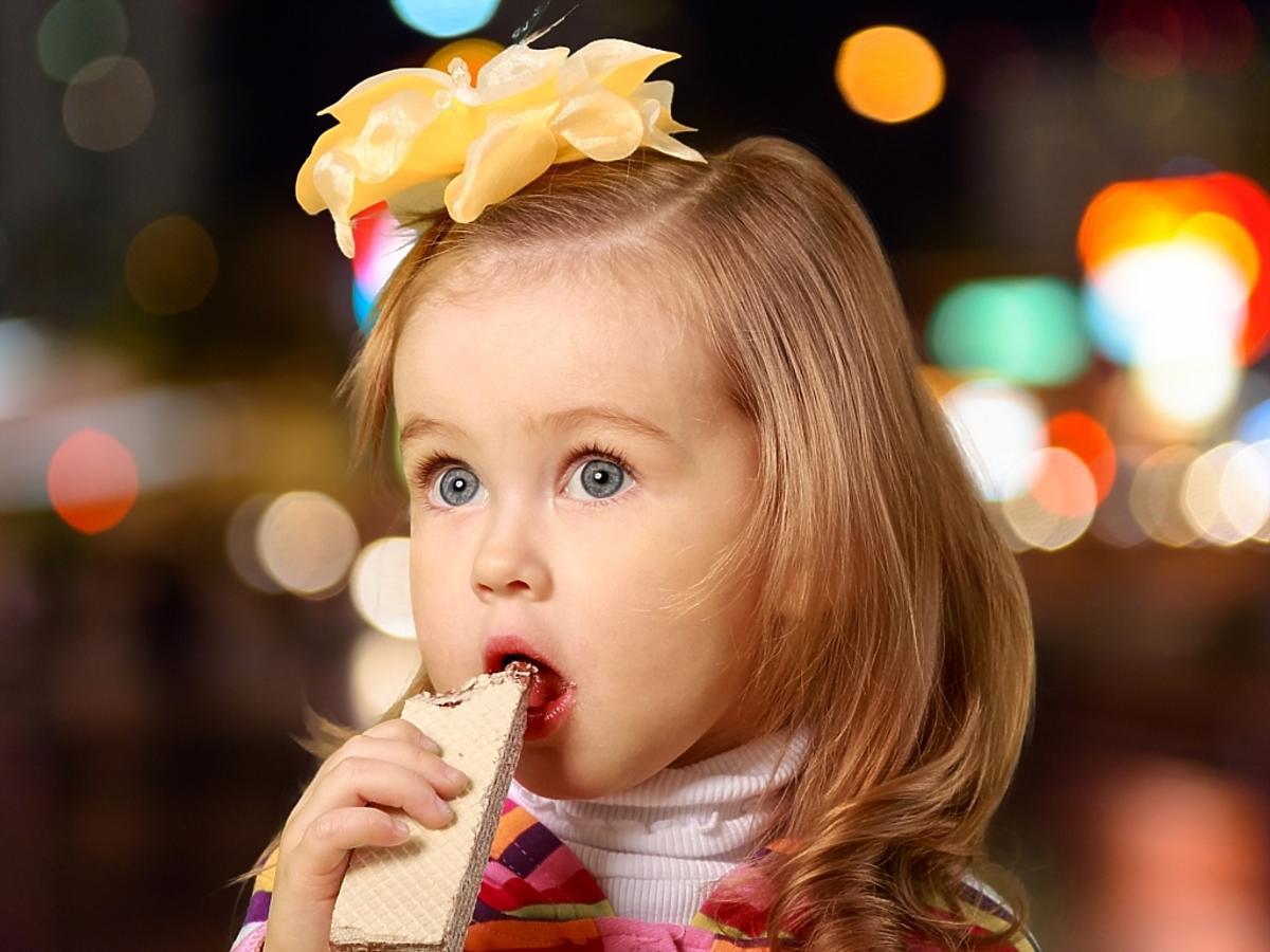 Dziewczynka z kokardą na głowie zjada wafelka.