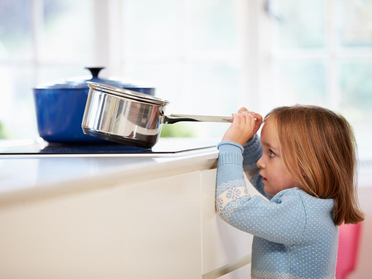 Dziewczynka zdejmuje garnek z kuchenki