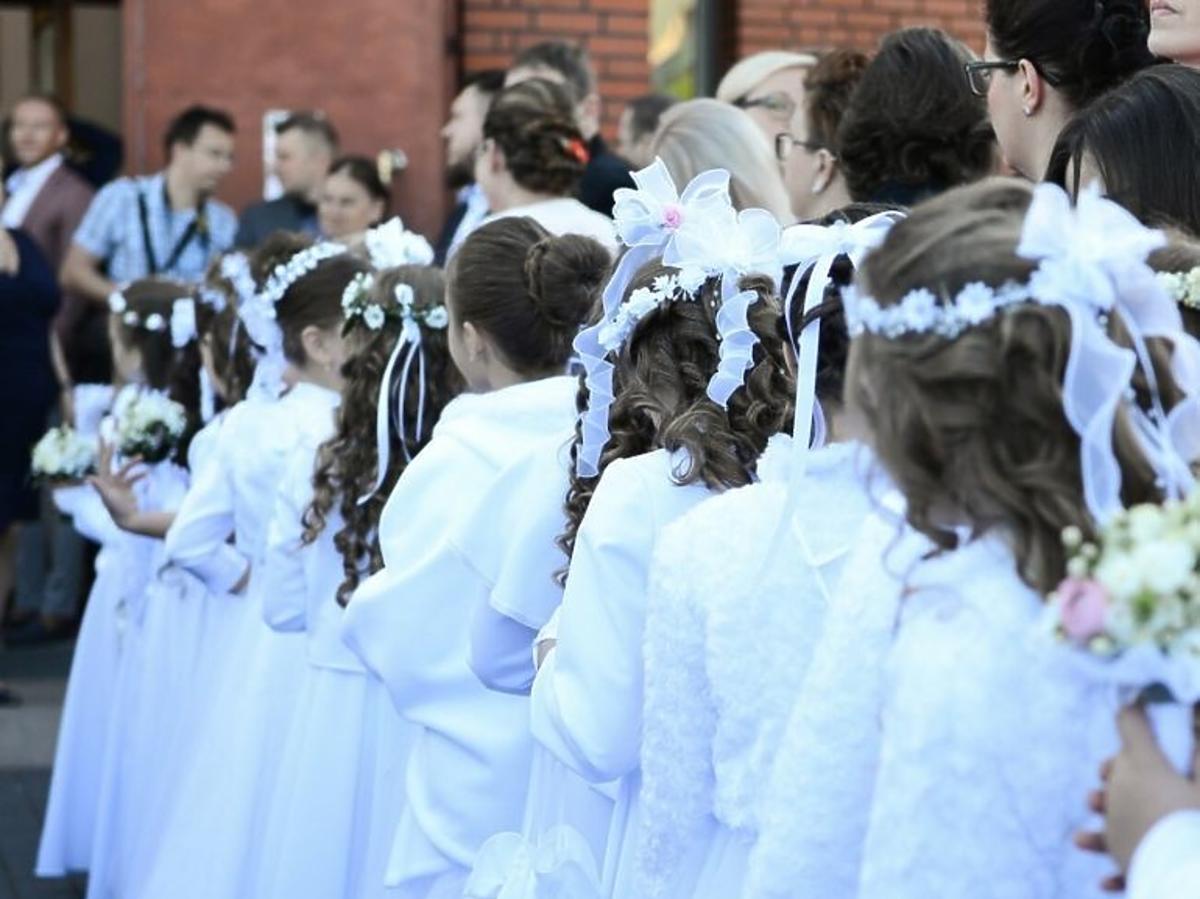 Dziewczynki w białych sukienkach w dniu pierwszej komunii