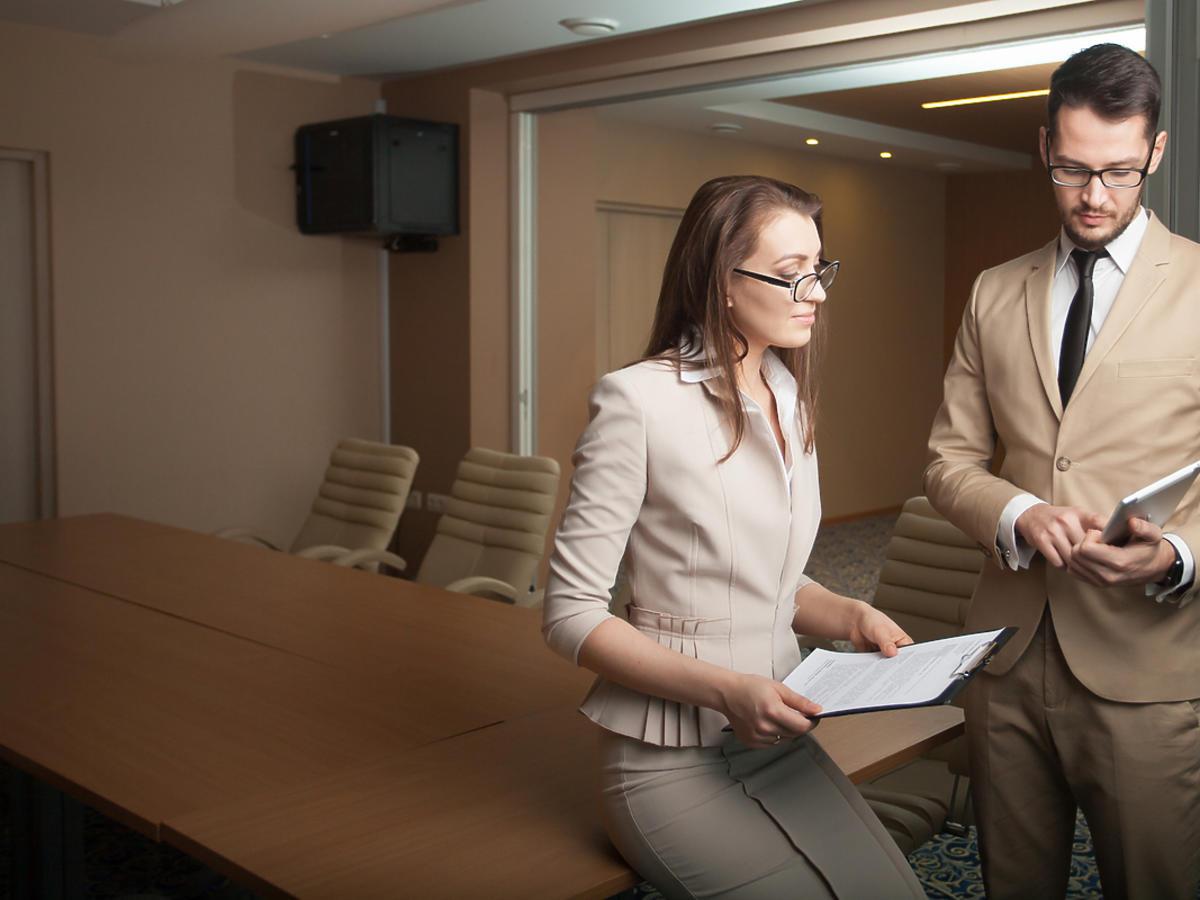 Elegancko ubrana kobieta dyskutuje z mężczyzną nad ważynym projektem w pracy.
