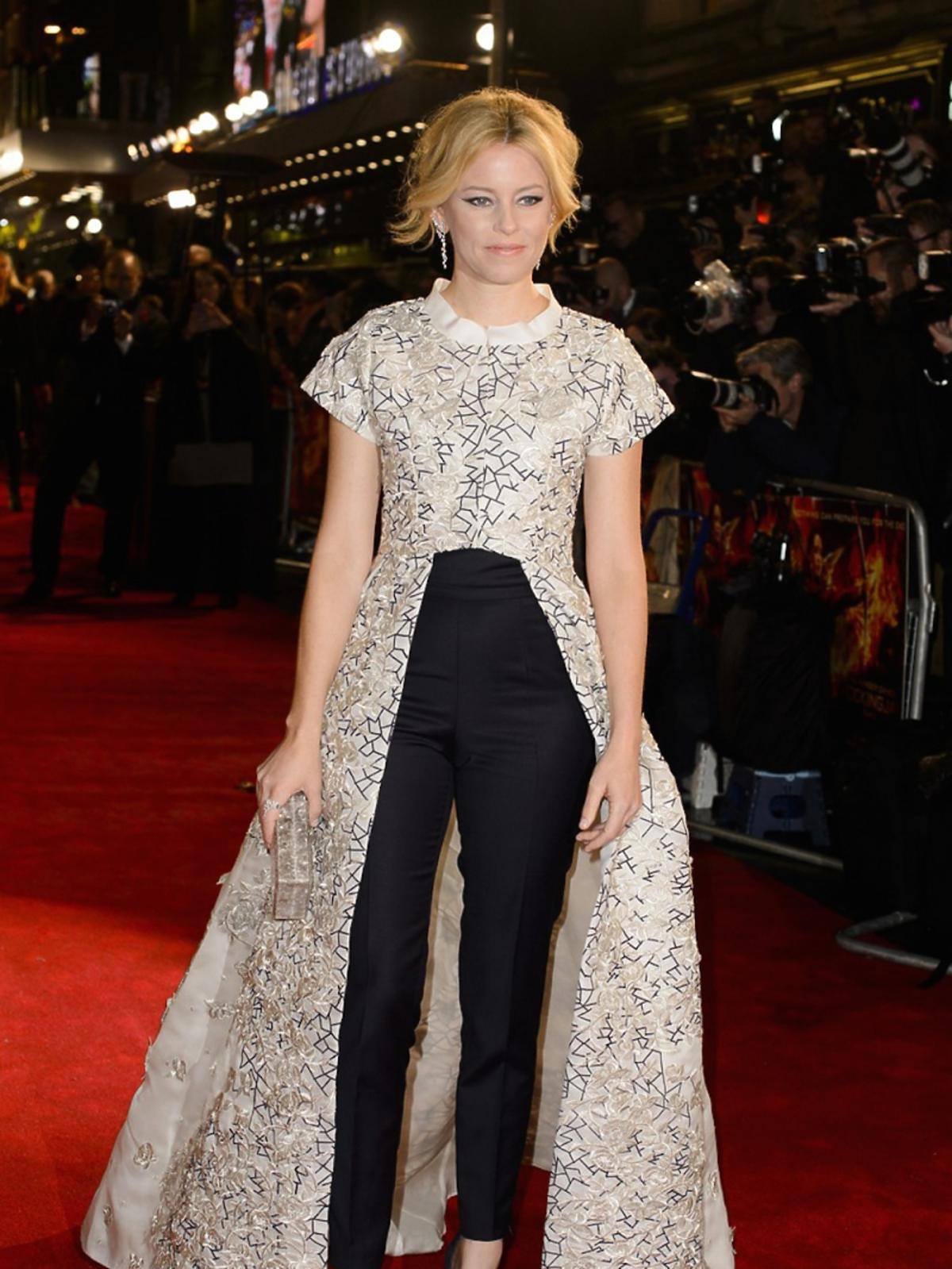 Elizabeth Banks wczarnych spodniach, białej sukni z czarne wzory