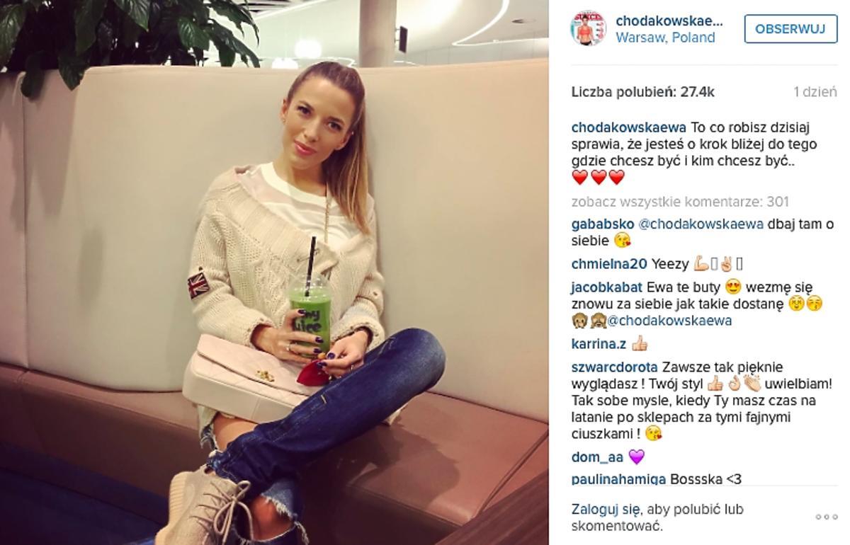 Ewa Chodakowska w beżowych sportowych butach, podartych dżinsach, jasnym swetrze