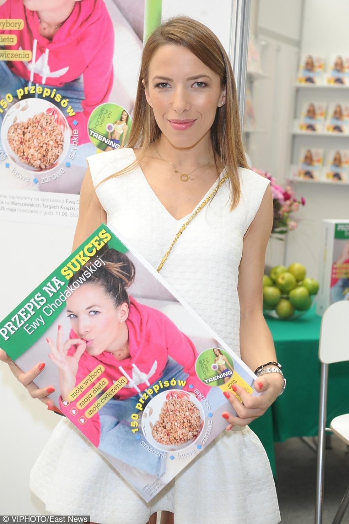 Ewa Chodakowska w białej sukience na targach książki promuje książkę Przepis na sukces swojego autorstwa