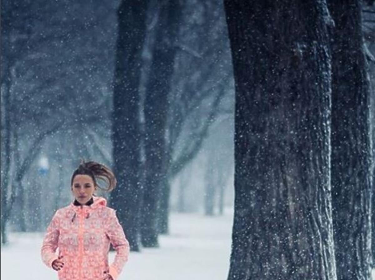 Ewa Chodakowska w brzoskwiniowej bluzie biega w śniegu