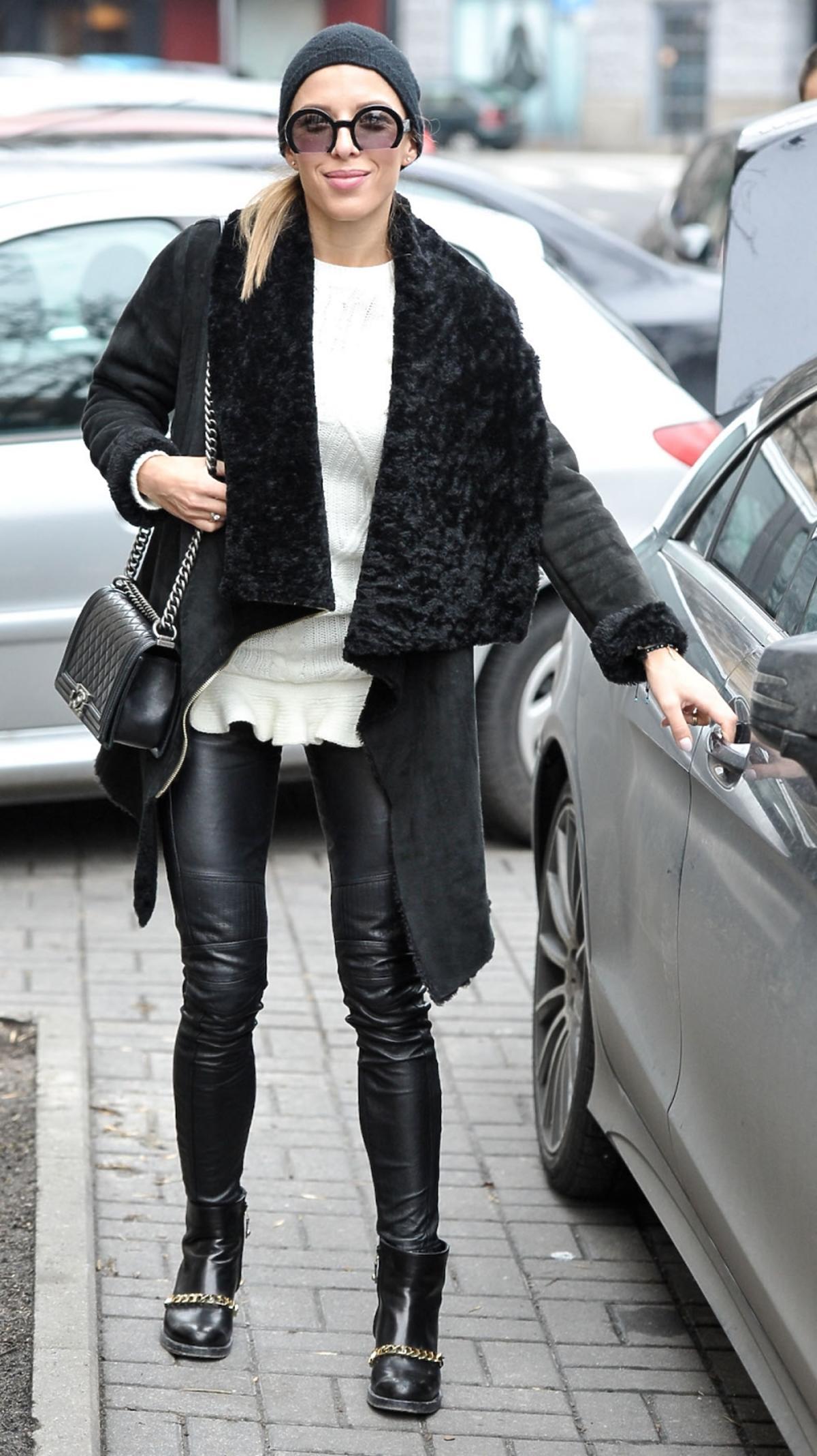 Ewa Chodakowska w czarnym płaszczy spodniach i czapce z pikowaną torebkąna łańcuszku