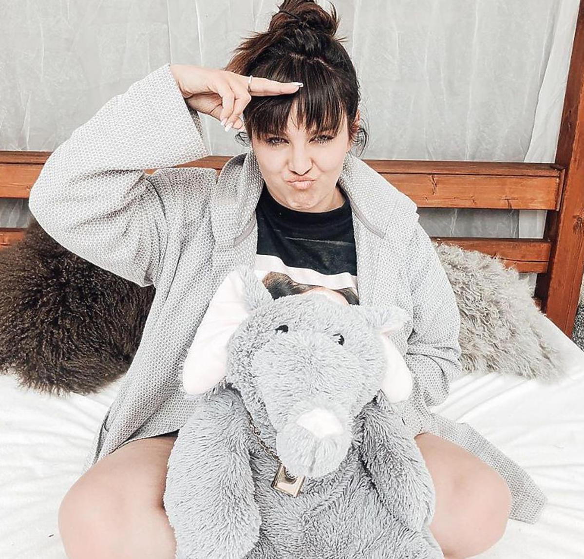 Ewa Farna na łóżku w szarej bluzie