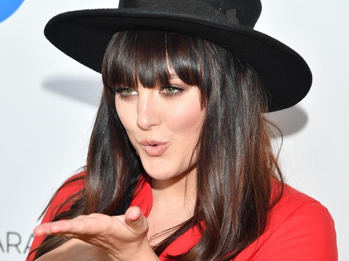Ewa Farna w czerwonej sukience i czarnym kapeluszu