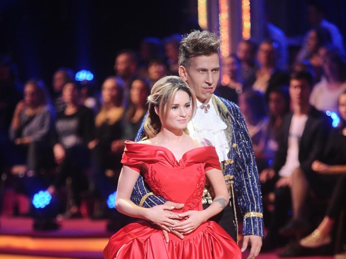 Ewelina Lisowska w czerwonej sukience z krynoliną i Tomasz Barański we fraku i z zębami wampira