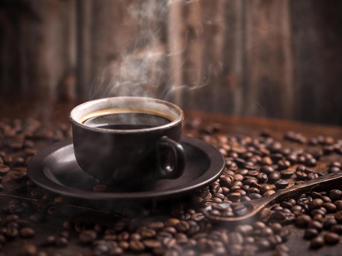 Filiżanka parującej kawy na ziarnach kawy