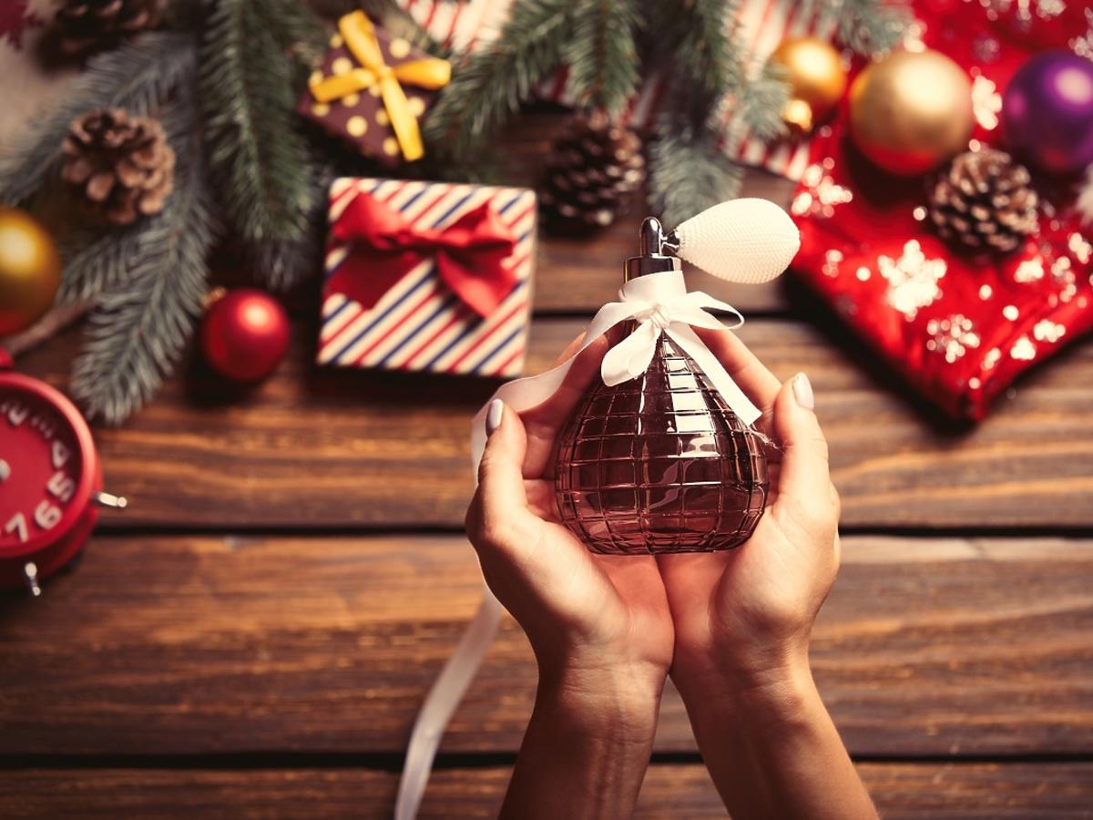 flakon perfum trzymany w rękach na tle świątecznych ozdób