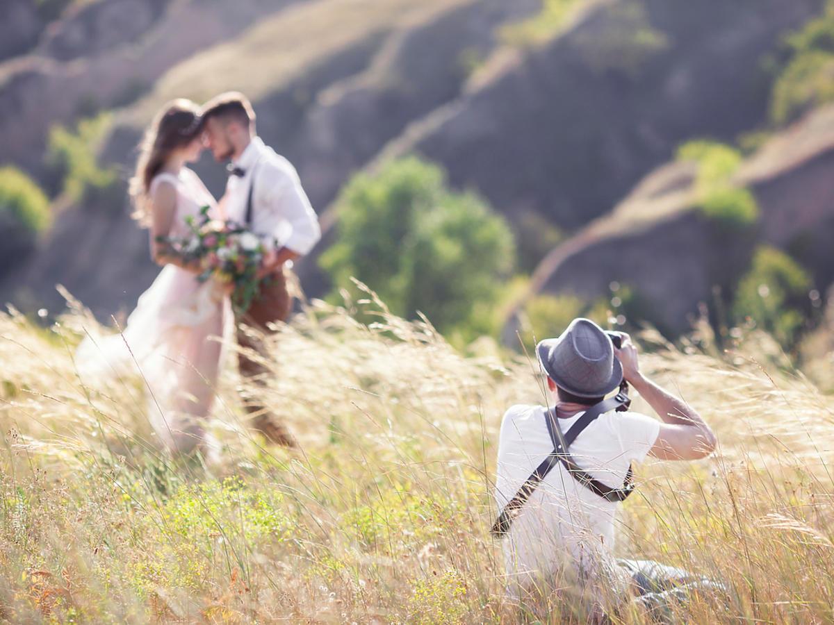 Fotograf robi parze zdjęcia ślubne w plenerze.