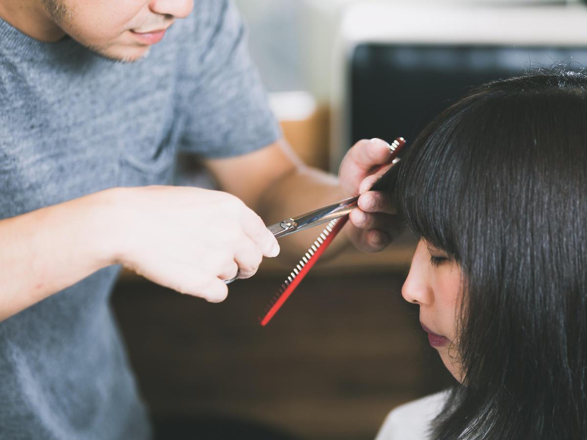 Fryzjer obcina grzywkę młodej dziewczynie.