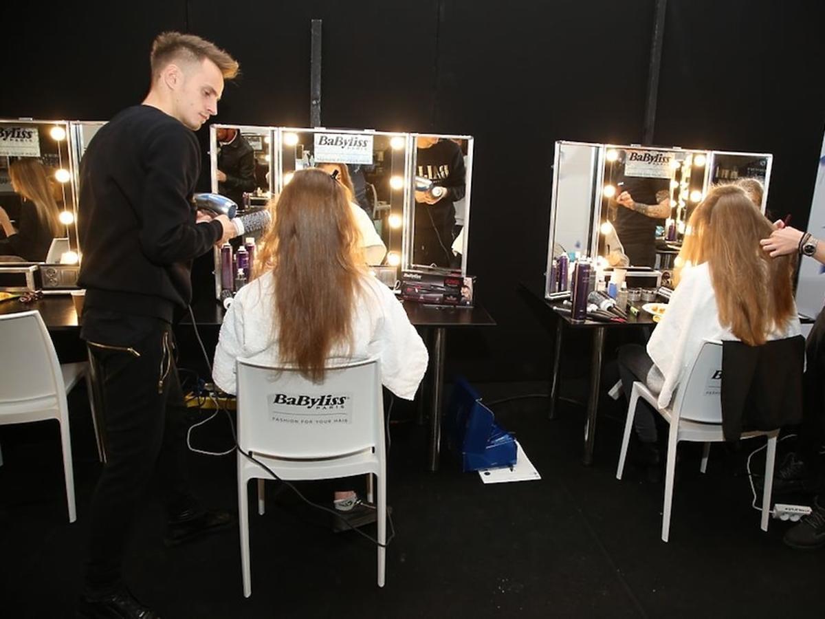 Fryzjerzy czeszą modelki na backstage'u