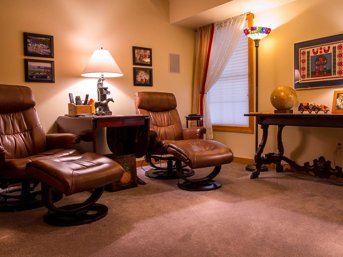 Gabinet z wygodnymi skórzanymi fotelami, utrzymany w tonacji brązu i beżu
