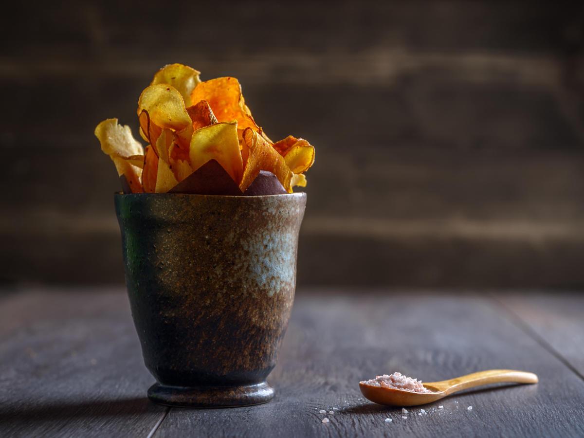 Garść chipsów zrobionych z ogórka leży w misce na stole.