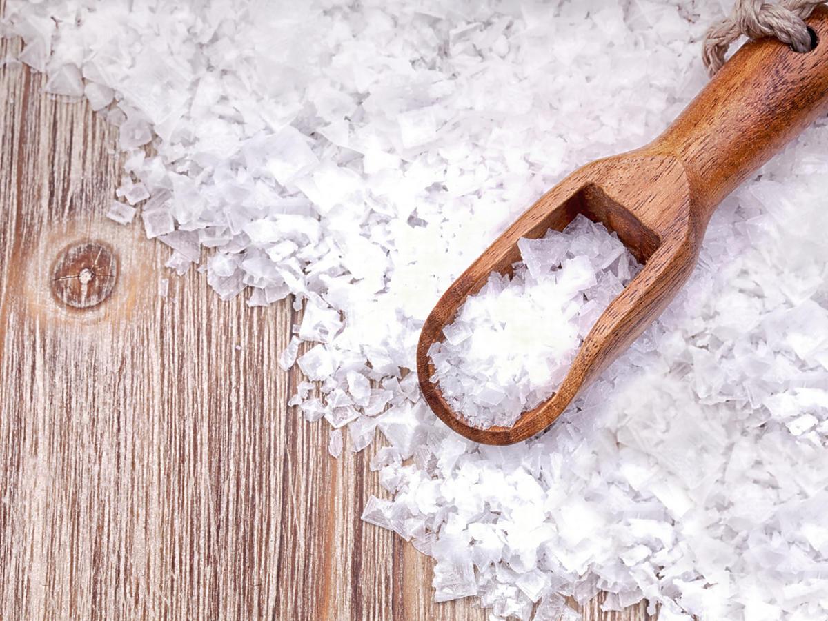 Grube kawałki soli morskiej na drewnianej szufelce