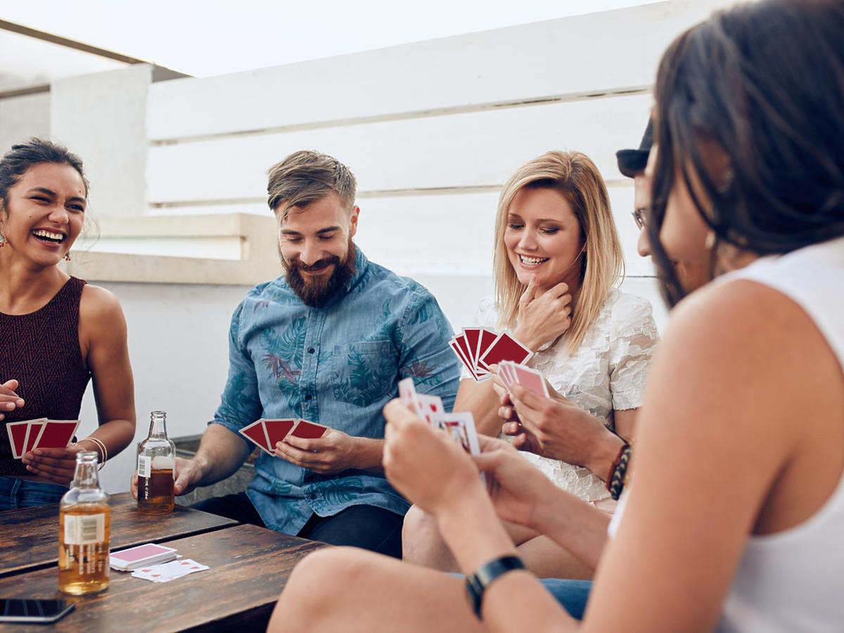 Grupa dorosłych osób gra w karty przy stole.