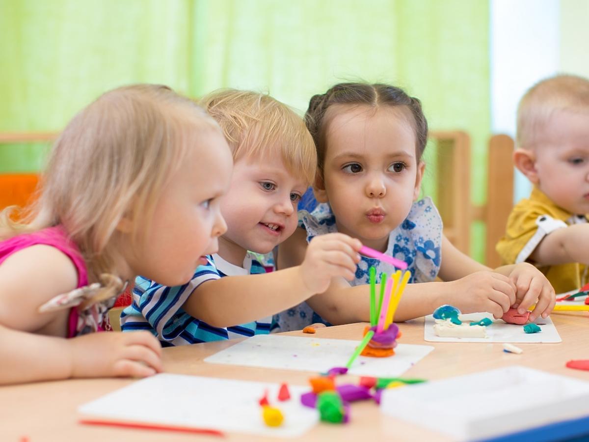 Grupa małych dzieci bawi się przy wspólnym stole.
