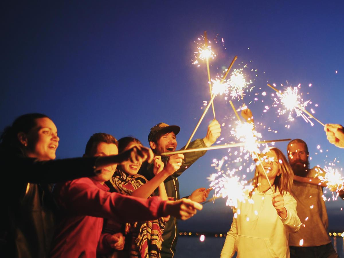 grupa przyjaciół z zimnymi ogniami nad wodą