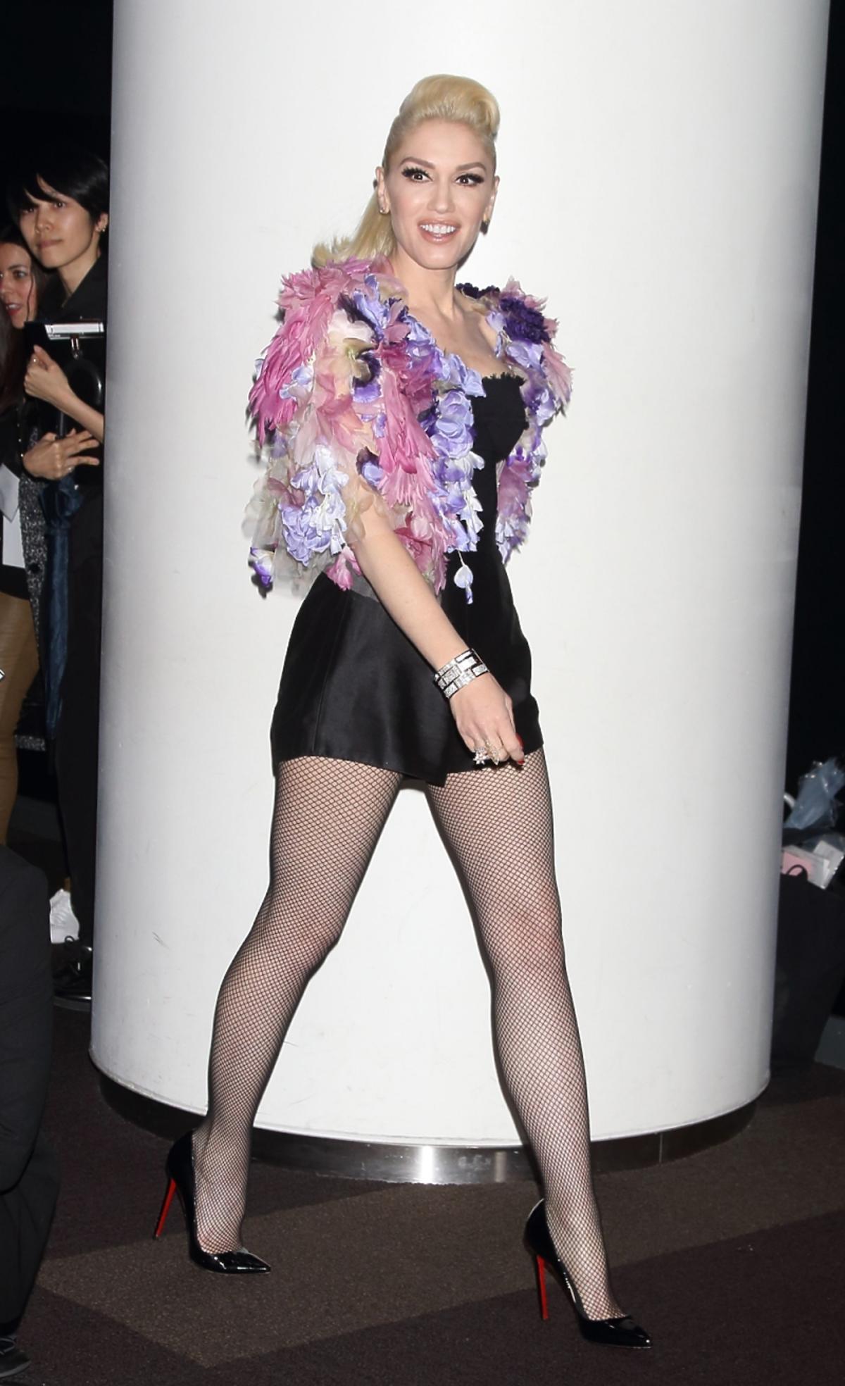 Gwen Stefani w kabaretkach, czarnym krótkim kombinezonie i różowym bolerku